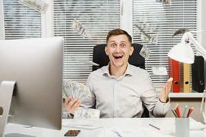 Happy smiling business man in shirt sitting at the desk with lot of cash money, working at computer with modern monitor, documents in light office on window background. Manager or worker winner.