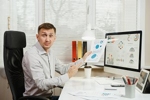 Shocked perplexed and stress business man in shirt sitting at the desk, working at computer with modern monitor, folders, coffee, documents in light office on window background. Manager or worker.