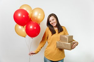 Beautiful caucasian fun young happy woman in yellow clothes, holding birthday red balloons, golden gift boxes with present, celebrating holiday party on white background isolated for advertisement.