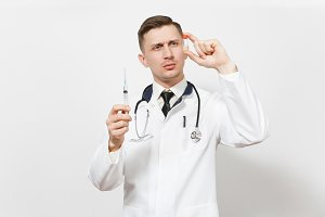 Serious young doctor man isolated on white background. Male doctor in medical uniform, stethoscope looking on liquid medicine in bottle, syringe with needle. Healthcare personnel, medicine concept.