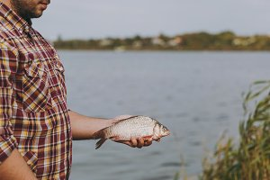 Close up unshaven man in checkered shirt with rolled up sleeves caught fish, holds it in arms on shore of lake on background of water, shrubs, reeds. Lifestyle, fisherman recreation, leisure concept.
