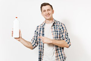 Young housekeeper man in checkered shirt holding white empty cleaning bottle with cleaner liquid isolated on white background. Male and house chores. Copy space advertisement. Cleanliness concept.