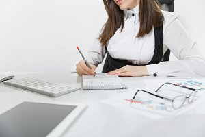 Close up portrait of serious brown-hair business woman in suit and glasses sitting at the desk, writing with pencil in notebook, working at computer with documents in light office, on white background