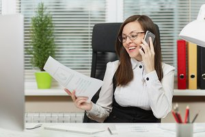 Beautiful smiling business woman in suit and glasses sitting at the desk, working at contemporary computer with documents in light office, talking on mobile phone, conducting pleasant conversation