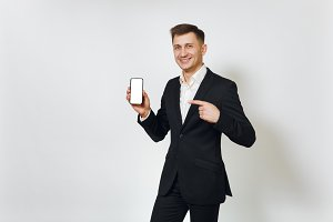 Young successful handsome rich business man in black suit pointing at modern mobile phone isolated on white background for advertising. Concept of money, achievement, career and wealth in 25-30 years.