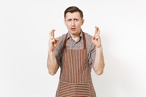 Concerned man chef or waiter in striped brown apron, shirt isolated on white background. Male housekeeper or houseworker keeping fingers crossed. Domestic worker for advertisement. Making a wish.