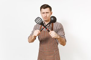 Young warlike man chef or waiter in striped brown apron, shirt holding black ladle or kitchen spoon, spatula isolated on white background. Male housekeeper or houseworker. Kitchenware, cuisine concept