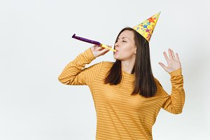 Beautiful caucasian fun young happy woman in yellow clothes and birthday party hat with brown long hair, playing pipe, celebrating and enjoying holiday on white background isolated for advertisement.