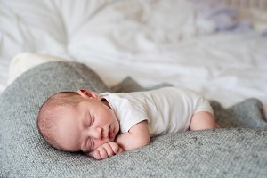 Newborn baby boy lying on bed, sleeping, close up