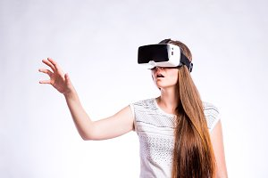 Woman with virtual reality goggles. Studio shot, gray background