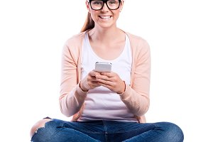 Woman with smartphone sitting on the floor, studio shot, isolate