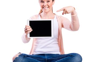 Woman with tablet sitting on the floor, studio shot, isolated