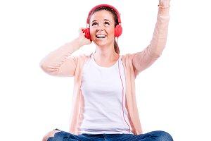 Woman with earphones sitting on the floor, studio shot, isolated