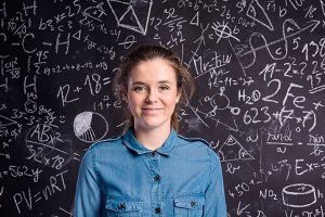 Girl in denim shirt against big blackboard with formulas