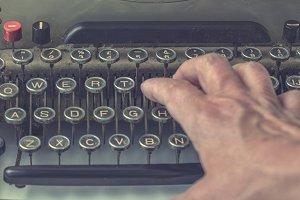 Hand on vintage typewriter