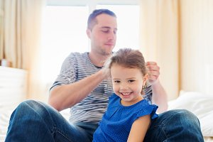 Father combing hair of his daughter in the morning