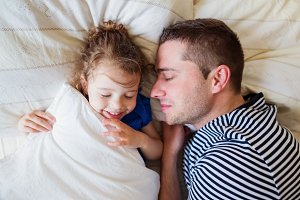 Father and daughter lying in parents bed, sleeping, smiling
