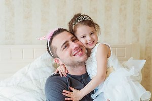 Cute little girl with her father wearing crowns