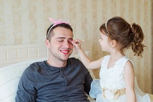 Cute girl putting on make up on her father