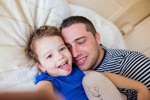 Father and daughter lying in parents bed, taking selfie