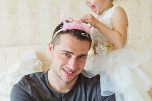 Cute girl putting a crown on her father head