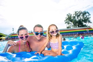 Mother, father and daughter in swimming pool. Sunny summer.