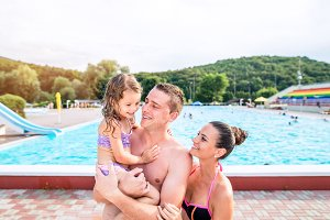 Mother, father and daughter near swimming pool. Sunny summer.