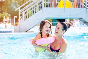 Mother and daughter in swimming pool, aquapark. Sunny summer.