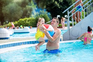 Father with his daughter in swimming pool. Sunny summer.