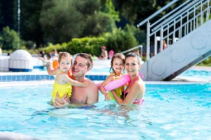 Mother, father and daughters in swimming pool. Sunny summer.
