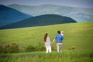 Young family on a walk against green fields and hills