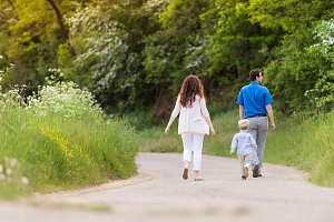 Young family walking on country road in green nature