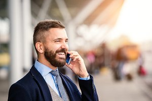 Hipster businessman making phone call waiting at the airport