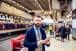 Close up, hipster businessman with tablet, train station