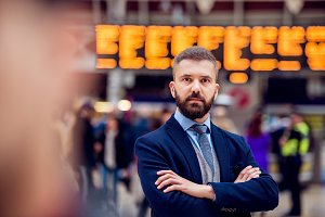 Hipster businessman waiting at the crowded London train station