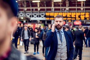 Busy businessman with smartphone, making phone call, crowded sta