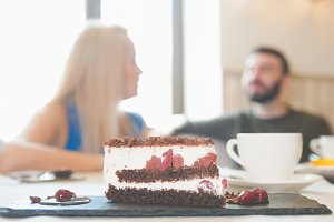 Sweet cake in front of couple sitting in a cafe enjoying conversation