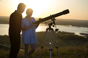 Young loving couple watching through telescope on the hill at