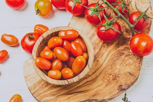 Fresh cherry tomatoes on olive wooden bowls and board, white background, top view