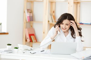 Serious well-dressed saleswoman talking on phone in office behind her desk and laptop computer. Copy space