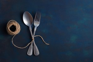 Vintage set of spoon and fork connected linen thread on a blue background. Time bound fork and spoon. Copy space