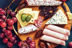 Various snacks on a wooden board, fruits, cold meat, sausage, cheese, dates, olives, jerky. Red wine in glasses and appetizer on a blue background, top view.