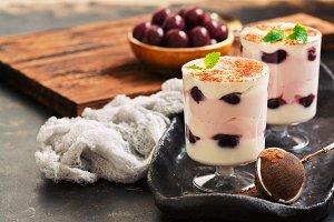 Layered dessert in glasses with yoghurt and canned cherries, sprinkled with cocoa powder and crumpled with mint leaves.