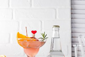 Margarita cocktail with rosemary, fresh orange and grapefruit juice with a bottle of tonic and a place under the text on the bottle on wooden background