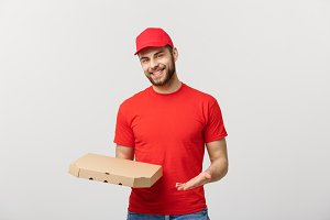 Delivery Concept: Young haapy caucasian Handsome Pizza delivery man holding pizza boxes isolated over grey background