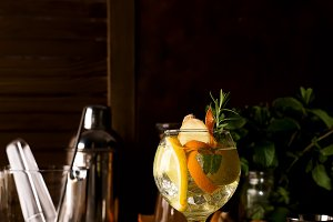Cocktail with rosemary, lemon and orange on dark wooden backgorund