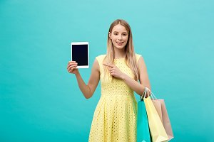 Happy attractive caucasian woman pointing finger on tablet and holding shopping bag at copy space isolated over blue background