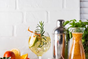 Fresh mojito drink with rosemary, lemon and orange on white wooden backgorund, copy space