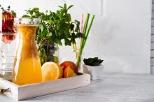 Orange lemonade in the decanter on a wooden tray with ftuits and mint by Yuliia Mazurkevych in Food & Drink