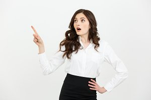 Business Concept: Portrait of surprised young businesswoman pointing finger away to copy space. Isolated on a white background.